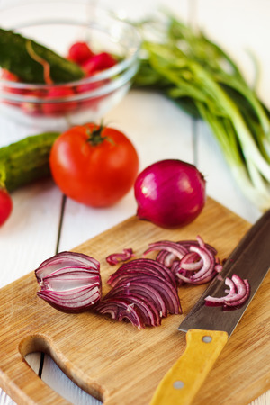 side order: Fresh vegetables for salad: cucumbers, tomatoes, radishes and onion on wooden background.
