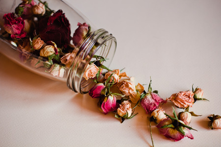 open the jar of dried roses lying on white background