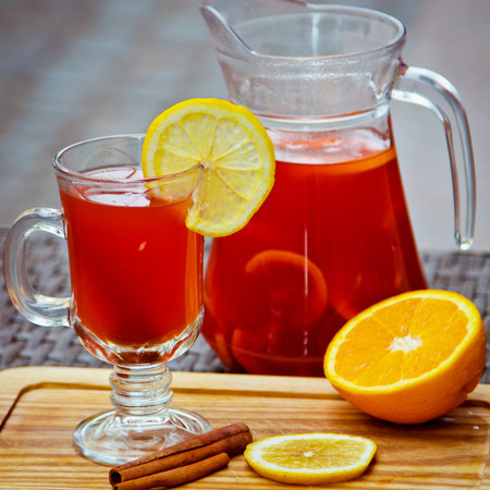 Refreshing summer fruit lemonade with orange and cinnamon in a beautiful glass and jar on wooden background Stok Fotoğraf