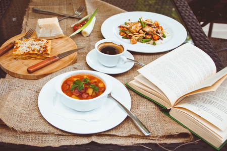 business cloth: Business lunch with soup, salad and coffee served at the table in the restaurant. On the cloth lay the glasses and the book Stock Photo