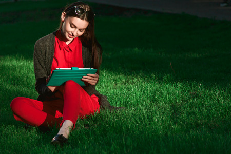 conceived: Young beautiful woman in red blouse, pants and sunglasses sitting on green grass in Park with tablet Stock Photo