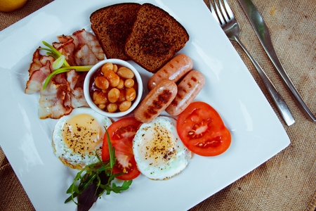 beans on toast: Traditional Full English Breakfast - sunny-side-up fried eggs, sausages, beans, toast and bacon Stock Photo