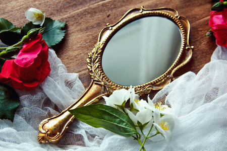 Beautiful a vintage mirror with flowers on wooden background