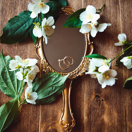 shine background: Beautiful wedding rings on a vintage mirror with flowers