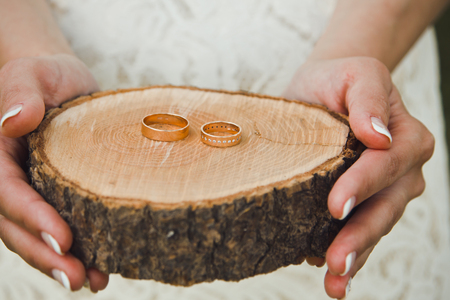 ring stand: the bride with a French manicure holds Beautiful engagement ring lie on wooden stand