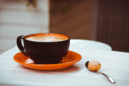macchiato: Beautiful cup of cappuccino with foam and coffee spoon stands on the table Stock Photo