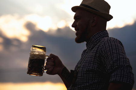Happy smiling man tasting fresh brewed beer against the sky at sunset.