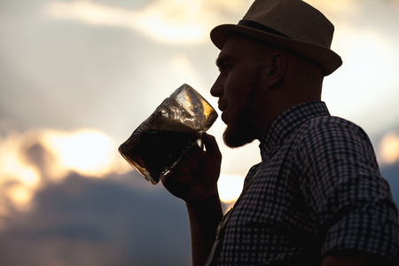 prost: Happy smiling man tasting fresh brewed beer against the sky at sunset.