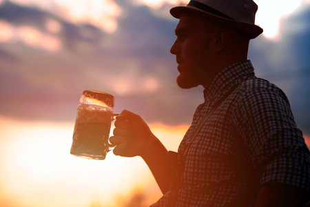 Happy smiling man tasting fresh brewed beer against the sky at sunset. The theme is Oktoberfest, a guy in Bavarian style