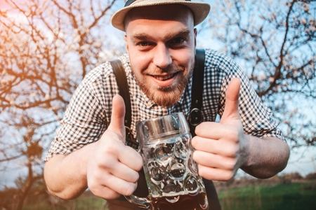 Happy smiling man with fresh brewed beer on the background of a blooming garden looking at the camera and shows that all is well. The theme is Oktoberfest, a guy in Bavarian style