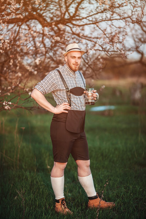 prost: Happy smiling man tasting fresh brewed beer on the background of a blooming garden. The theme is Oktoberfest, a guy in Bavarian style Stock Photo