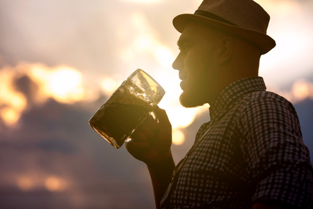 prost: Happy smiling man tasting fresh brewed beer against the sky at sunset. The theme is Oktoberfest, a guy in Bavarian style