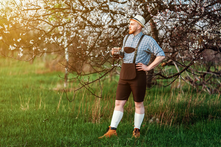 Happy smiling man tasting fresh brewed beer on the background of a blooming garden. The theme is Oktoberfest, a guy in Bavarian style Stock Photo