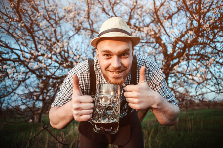 prost: Happy smiling man with fresh brewed beer on the background of a blooming garden looking at the camera and shows that all is well. The theme is Oktoberfest, a guy in Bavarian style
