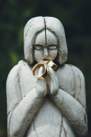 stylish pair of golden wedding ring on the old statues woman, time concept Stock Photo