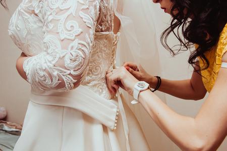 Beautiful bridesmaid tying bow on wedding dress