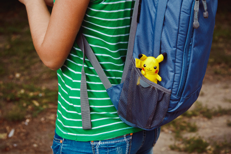 Victory Park in Poltava, Ukraine - September 03.09.2016: plush doll Pikachu in the pocket of a backpack girl. Toy Pokémon from the famous cartoon and game pokemon go.