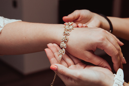 Bridal preparation, bride putting on jewelry, focus on bracelet