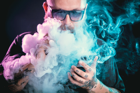non violence: Men with beard  in sunglasses vaping and releases a cloud of vapor.