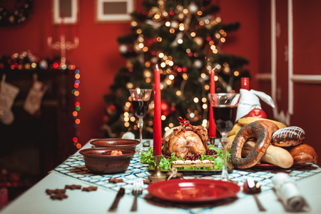 Christmas dinner by candlelight, table setting. Thanksgiving table with baked turkey in a decorated room with a Christmas tree. Фото со стока