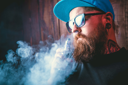 Men with beard  in sunglasses vaping and releases a cloud of vapor. Reklamní fotografie - 65310855