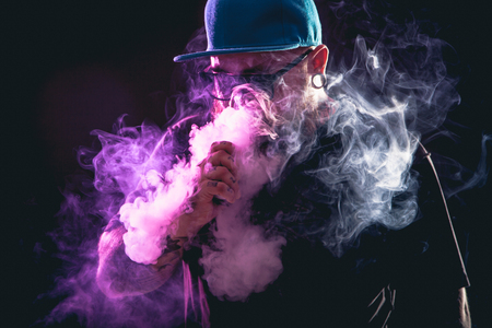 Men with beard  in sunglasses vaping and releases a cloud of vapor. 版權商用圖片 - 65310858
