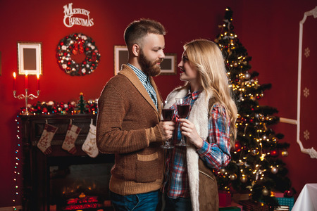 lovingly: Attractive happy couple on Christmas day standing in front of the decorated tree smiling lovingly into each others eyes and holding glasses with red wine