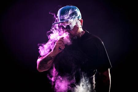 vaping 선글라스에 수염을 가진 남자 증기의 구름을 출시.