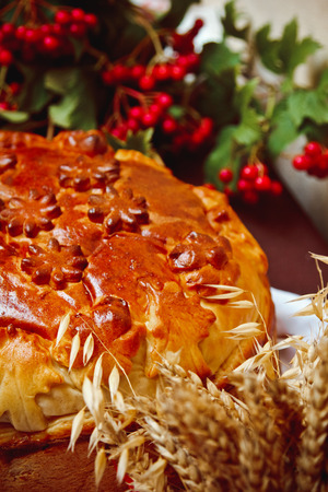 A nice loaf with viburnum berries and ears of wheat Stock Photo
