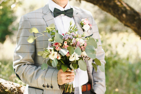arm bouquet: groom hold beautiful wedding bouquet in hand