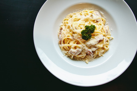 pancetta cubetti: Classic Pasta carbonara Italian with Parmesan Cheese on black background