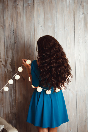 kinky: Beautiful young girl in a blue dress and long hair with a Christmas garland from the back Stock Photo