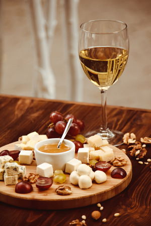 cheeseboard: Cheese Board served with grapes, nuts and a glass of white wine on a wooden background Stock Photo