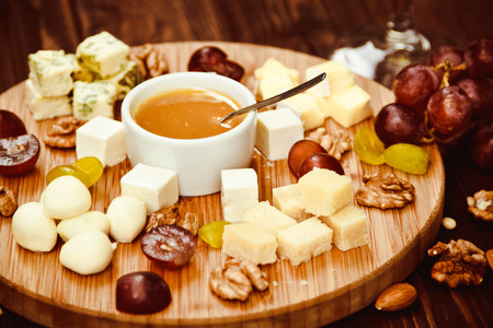 tabla de quesos: Cheese Board served with grapes and nuts on a wooden background Foto de archivo