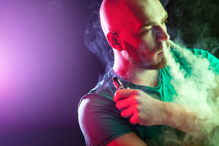 Men with beard  in sunglasses vaping and releases a cloud of vapor.Men with beard  in sunglasses vaping and releases a cloud of vapor. Stock Photo