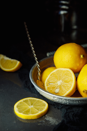 Beautiful ripe lemons in plate on a black background Reklamní fotografie
