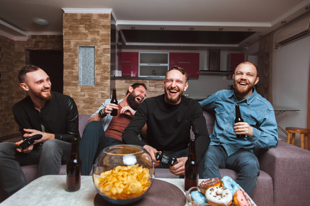 A company of four men having fun and laughing sitting on the couch at home with beer and chips, two of them with joysticks in hand playing computer video game. The concept of friendship, technology and weekend Stock Photo
