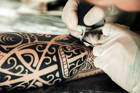 Master tattoo artist in gloves makes tattoo on hand men Stock Photo