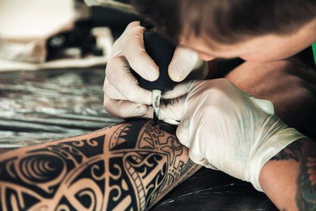 Master tattoo artist in gloves makes tattoo on hand men Фото со стока