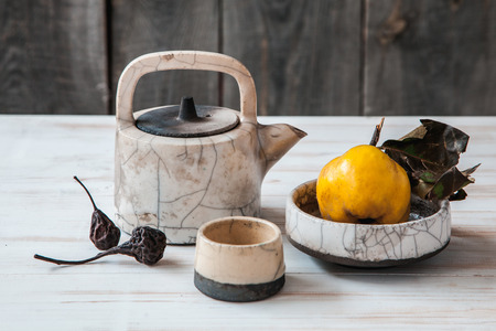 Old ceramic kettle with quinces and dried pears on wooden background