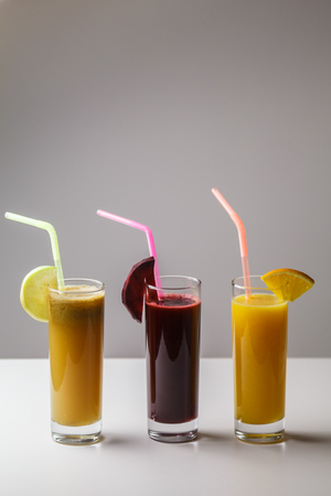 Healthy eating juicing cleanse diet trend concept - fruit and vegetable juice glasses with straw. Theme of raw food, live food background