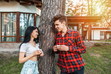 The guy with the girl talking and smiling, looking into each others eyes, holding coffee in his hands. The concept of pure love, the beginning of a relationship, the flirting and shyness. Beautiful young couple during a romantic date. Stock Photo
