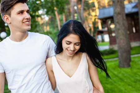 The guy hugs the waist of the girl with a shy smile while walking in nature. Beautiful young couple during a romantic date. Stock Photo