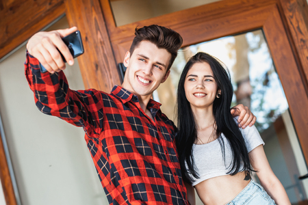 intriguing: Happy romantic couple taking a photo with smart phone. Beautiful young girl and man hug and laugh taking a selfie. Urban fashion style