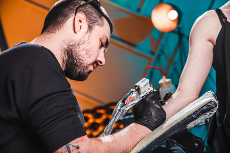 master tattooist makes a tattoo on the skin of the hand client girl in a workshop with special equipment