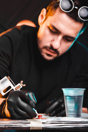 master tattoo artist prepares tools for tattooing