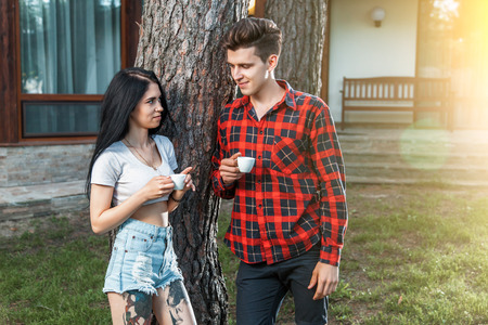 The guy with the girl talking and smiling, looking into each others eyes, holding coffee in his hands. The concept of beginning of a relationship  and flirting. Beautiful young couple during a romantic date.