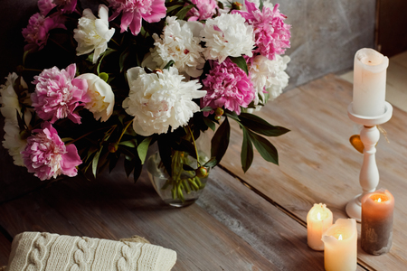 Beautiful romantic interior in loft style with candles and a bouquet of peonies