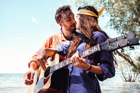 Beautiful young couple in love in hippie style with the guitar resting on the beach in summer. A man kisses his girlfriend on the seafront