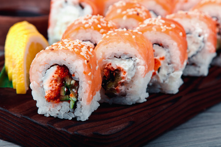 Philadelphia roll classic wiht  Salmon Philadelphia cheese cucumber avocado on the Board. Japanese sushi. Stock Photo
